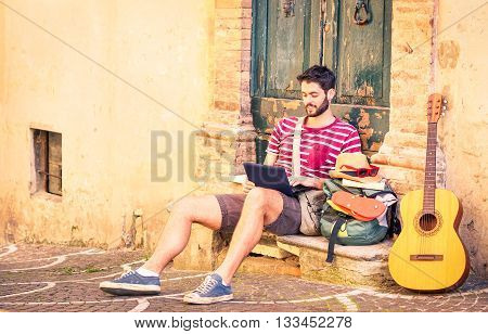 Handsome travel man using pc sitting in front of old house - Music artist relaxing at city alley - Concept of freedom and summer world tour backpacker style -