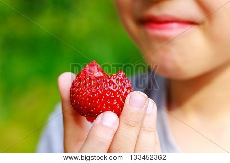 Girl bit off piece of strawberry and grimaced displeasure emotion focus on the berry poster