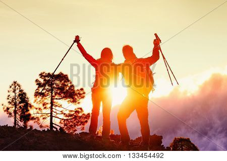 Successful hiking couple standing on mountain top during sunset cheering in success. Rear view of male and female hiker raising hiking poles against sky. Man and woman are celebrating during vacation.
