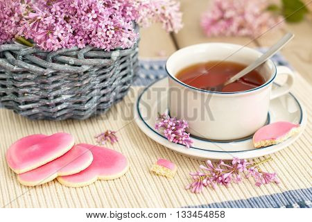 There are tea couple, bouquet of a lilac and pink cookies on a tea table