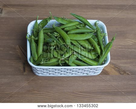 Many green peas in a white basket on the table