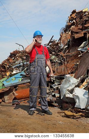 Recycling Industry, Worker Using Phone And Heap Of Old Metal