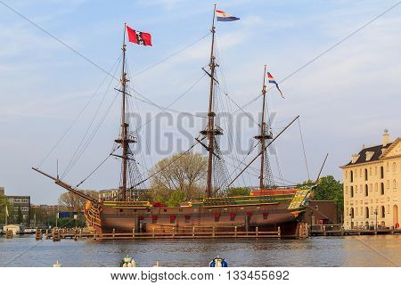 """AMSTERDAM, NETHERLANDS - MAY 6, 2013: This is ship """"Amsterdam"""" near the building of the Dutch National Maritime Museum."""