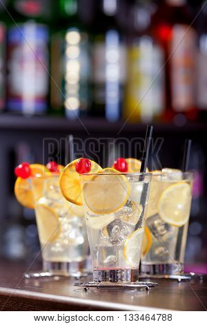 Four Tom Collins cocktails on a bar in a nightclub. Vertical shot