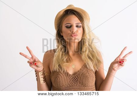 Closeup of gorgeous teenage blonde girl in crochet top with fringes, straw fedora hat and golden bracelet and flash tattoo, making kissy face, gesturing peace. No retouch, no filter, studio lighting.