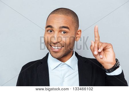 Close-up portrait of a happy young man pointing finger up at something interesting isolated on gray background