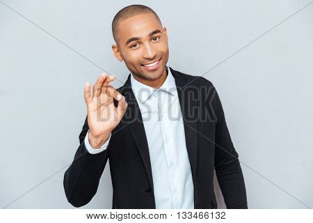Young hansome guy showing the okay sign isolated on the gray background