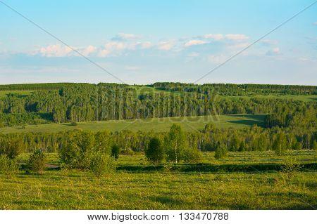 Summer sunset over beautiful green hills landscape. Beautiful landscape. Hillside landscape. Rolling hills. Hills and sky.