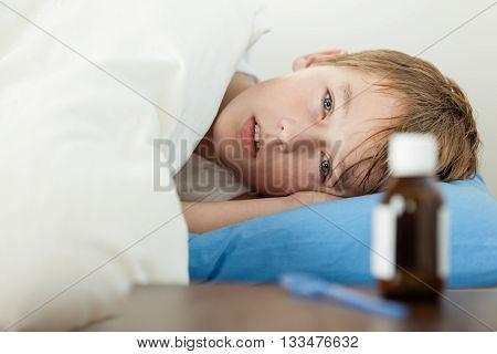 Feverish Boy Under Thick Blanket Beside Medicine