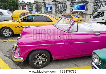 HAVANA - DECEMBER 10: American classic cars waiting for tourists on 10 December 2015 in Havana, Cuba. Brightly colored vintage American cars are very popular in Havana.