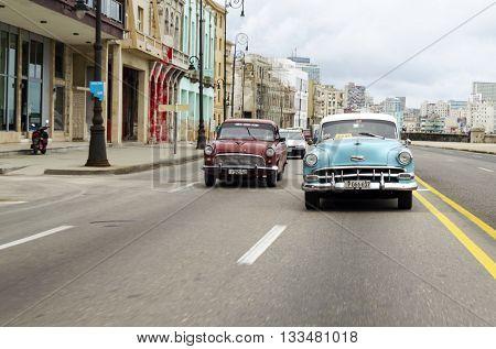 HAVANA - DECEMBER 10: American classic cars driving on the street on 10 December 2015 in Havana, Cuba. Brightly colored vintage American cars are very popular in Havana.