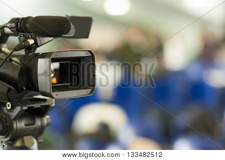 Front View of Professional Videocamera. Positioned Against Blurred Background. Horizontal Image