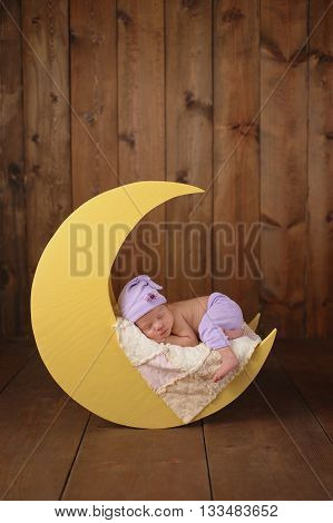 Studio portrait of an eleven day old newborn baby girl wearing pajama bottoms and a sleeping cap. She is sleeping on a moon shaped posing prop.