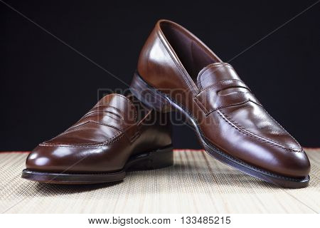 Footwear Concepts. Pair of Stylish Brown Penny Loafer Shoes Placed on Straw Surface against Black.Horizontal Shot