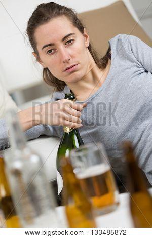drunk girl holding bottle of alcohol
