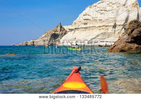 MELOS GREECE - SEPTEMBER 4 2012: People kayaking through rock formations off the south coast of Melos island near Gerontas headland.