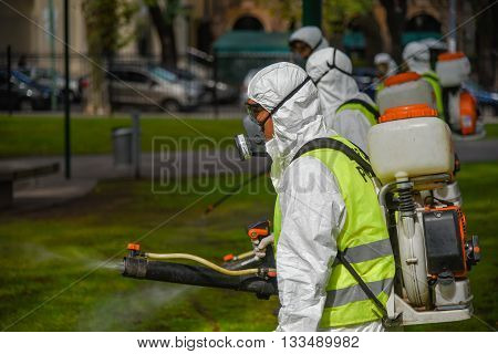 Buenos Aires Argentina - March 3 2016: Employees of the Ministry of Environment and Public Space fumigate for Aedes aegypti mosquitos to prevent the spread of zika virus and Dengue fever in park.