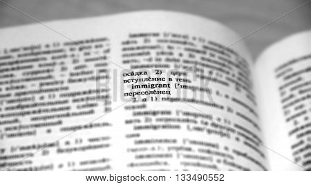 Immigrant Definition Word Text in Dictionary Page. Shallow depth of field. Russian language translate . Black and white image