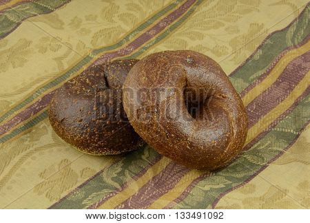 Two breakfast whole pumpernickel bagels on tablecloth