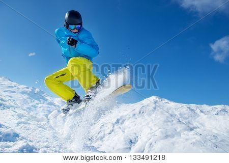 Winter vacation -  snowboarder jumping high in the air on a cold sunny day