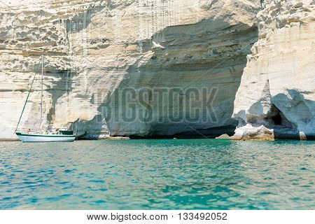 MELOS GREECE - SEPTEMBER 4 2012: A sailing boat anchored off a cave at Kleftiko. The caves and rock formations were used by pirates for hideouts.