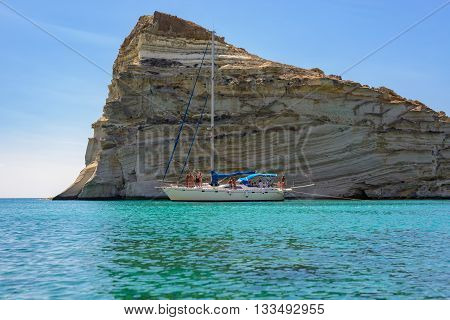 MELOS GREECE - SEPTEMBER 4 2012: Sailing boat with people behind one of the many imposing rock formations at Kleftiko. They were used in the past by pirates for hideouts.