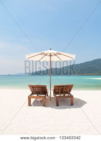 Two wooden deckchairs beneath a white parasol umbrella face out to an idyllic tropical sea on a paradise beach. Travel destinations escapism and vacations.