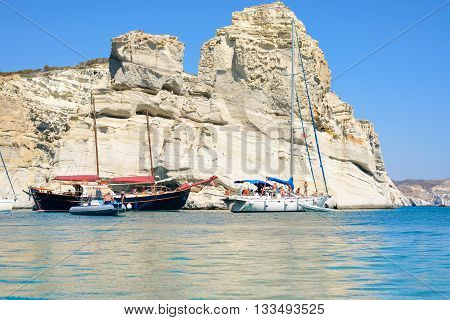 MELOS GREECE - SEPTEMBER 4 2012: Sailing boats with people behind one of the many imposing rock formations at Kleftiko. They were used in the past by pirates for hideouts.