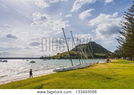 Tauranga New Zealand - November 20 2014: Mount Maunganui is extinct volcano that rises above the town of Tauranga. It is also known as the Mount. Adjacent to the Mount is a park where people relax. Sailing boat in the foreground in backlight.