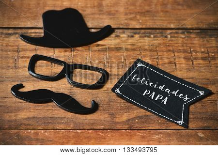 a black flag-shaped signboard with the text felicidades papa, congratulations dad in spanish, and a mustache, a pair of eyeglasses and a hat forming the face of a man, on a rustic wooden surface