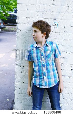 preteen handsome boy close up photo hiding around the corner play hide and seek game