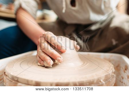Dirty potters hand on potters wheel. Artist works with wet clay. Front view on hand of craftsman on clay loam