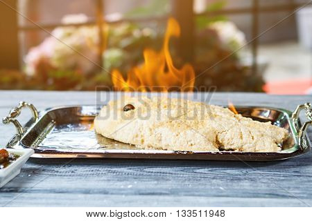 Burning fish on a tray. Breaded fish with black olive. Dorado fish cooked with fire. Fish fillet in sea salt.