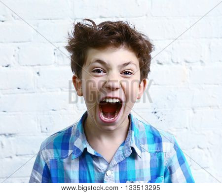preteen handsome boy shouting yelling close up portrait on the white wall background