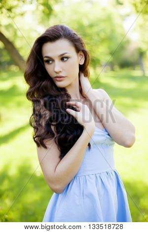 A portrait of a beautiful young caucasian woman outdoor. Soft sunny colors. Sweet girl, clean skin, long dark hair.