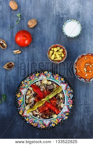 Traditional Turkish Bursa iskender kebap doner served with special red sauce and yogurt in the middle, garnished with grilled tomatoes and peppers
