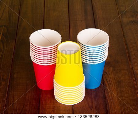 Bright disposable cups on the background of dark wood.