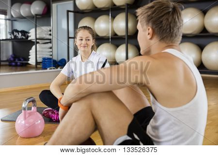 Woman Looking At Friend While Sitting In Gym
