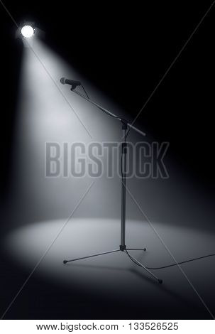 Microphone stand on stage lit by spotlight. 3d rendering