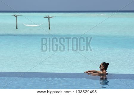 woman in turquise infinity pool in Anantara Resort Maldives