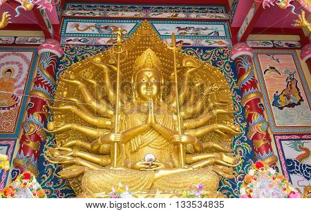 Golden Guanyin Buddha statue with thousand hands in Temple Thailand.