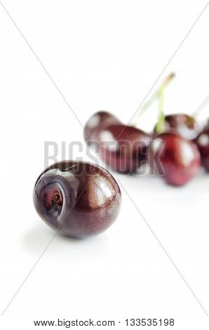 Sweet cherry berry in the foreground. The isolated object on a white background with a shadow. On a background group of objects in the small depth of sharpness. Vertical format. Indoors. Color. Photo.