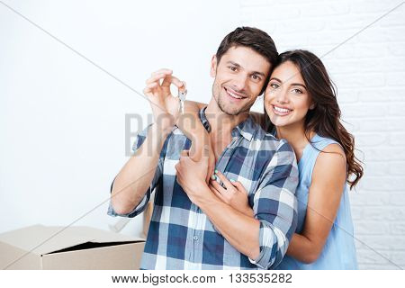 Young smiling couple showing keys to new home hugging looking at camera
