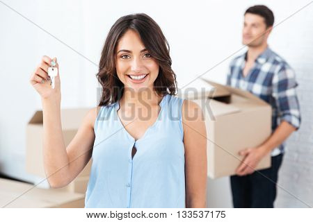 Happy married couple with key and boxes moving to new home