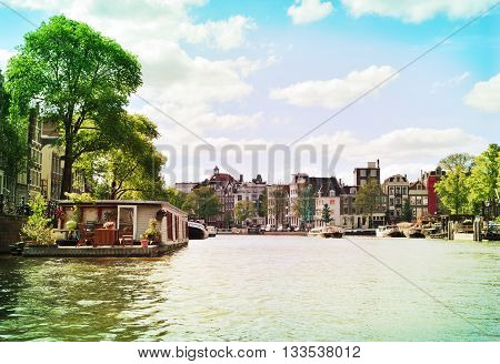 Canal at Amsterdam city, Netherlands. Boats and cityscape of Amsterdam at a a sunny day. Boats anchored at the canal and cityscape in the background.