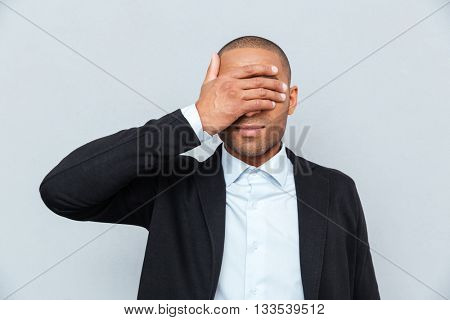 Portrait of a businessman covering eyes isolated on gray background