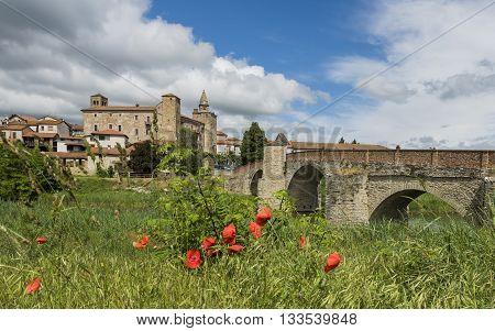 Roman Bridge people river houses and Church of Monastero Bormida in Piedmont Italy