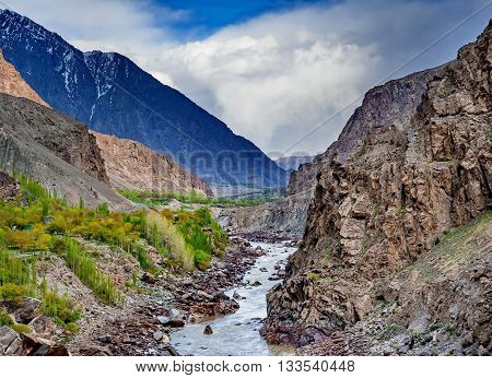 Hunza river flowing through the beautiful mountain valley in the northern part of the Karakorum mountains in Pakistan