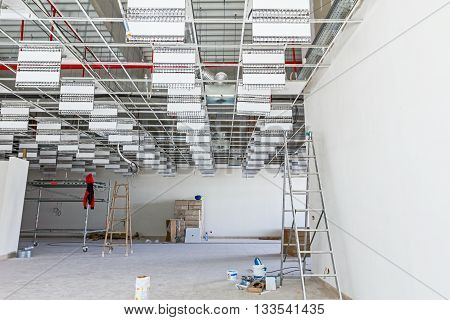 Workers are used wooden ladder to complete suspended office ceiling at building site.