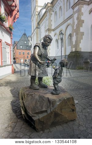 BOPPARD GERMANY 9 AUGUST 2014 - Bronze Statue of a lady selling candy to a child in Boppard Germany. Inscription; ERINNERING AN ALTE ZEITEN DAT SCHNUGGEL ELSJE VON JUTTA REISS 2001